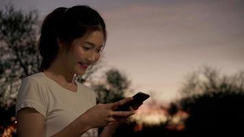 alegre mujer blogger turística asiática que usa tecnología de pantalla táctil en el teléfono inteligente mientras camina por la calle. video