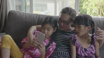 feliz familia asiática tomando selfie con smartphone.