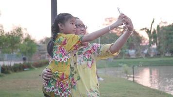 feliz família asiática tomando selfie com smartphone.