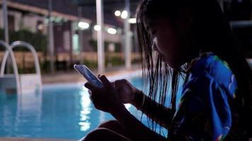 Chica de niños asiáticos con teléfono inteligente relajante junto a la piscina.