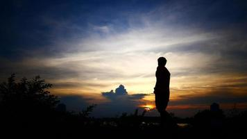 Silhouettes of relax man with the background of the sunset sky.