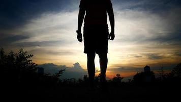 silhuetas do homem ganham no fundo do céu do sol video
