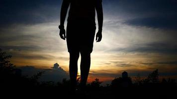 silhuetas do homem ganham no fundo do céu do sol