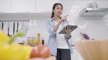 mulher asiática feliz usando o tablet para receita ao fazer comida na cozinha. video