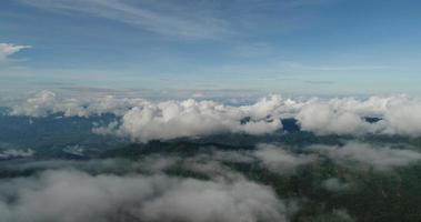 Aerial view wide shot point of view mountain with lush trees and foggy clouds
