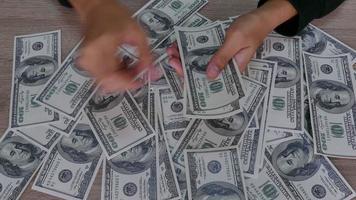 mãos contando notas de dólar na mesa