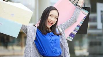 a garota sorri feliz na parada. ela se virou e mostrou um saco de papel.