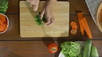 Vista superior de la mujer jefe haciendo ensalada de comida sana y picar pimiento en la tabla de cortar en la cocina. video