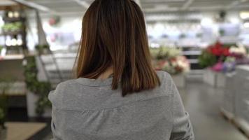 cámara lenta - joven asiática paseos en carro de compras eligiendo muebles nuevos en el almacén.