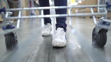 câmera lenta - jovem mulher asiática anda de carrinho de compras, escolhendo móveis novos no armazém. video