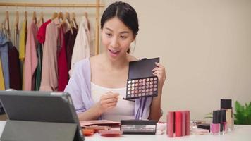 feliz hermosa joven asiática uso revisión de cosméticos maquillaje tutorial transmisión video en vivo a la red social.