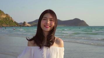 jeune femme asiatique marchant sur une plage.