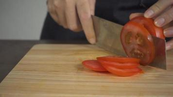 chef cortando un tomate video