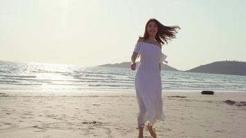jeune femme asiatique marchant sur la plage.