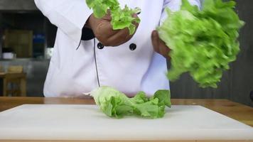 Cerca del hombre jefe haciendo ensalada de alimentos saludables y cortando lechuga en la tabla de cortar.