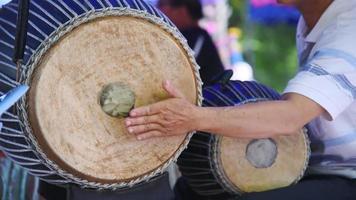 Músico asiático masculino tocando el tambor tailandés