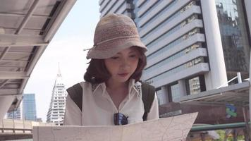 Young Asian backpacker looking for location on map.