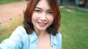 Blogger de mujeres asiáticas felices hermosas atractivas que usan el teléfono inteligente para autofotos y grabar videos de blogs de alimentos.