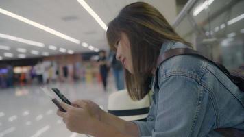 femme asiatique heureuse en utilisant et en vérifiant son smartphone assis sur une chaise dans le hall du terminal. video