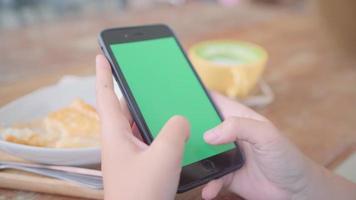 jovem mulher asiática usando dispositivo celular preto com tela verde.