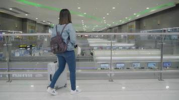 glückliche asiatische Frau, die ihr Smartphone in der Terminalhalle benutzt und überprüft.