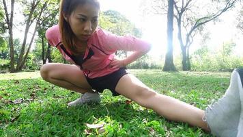câmera lenta - saudável mulher asiática, exercitando-se no parque. cabe jovem fazendo treino de treino de manhã.