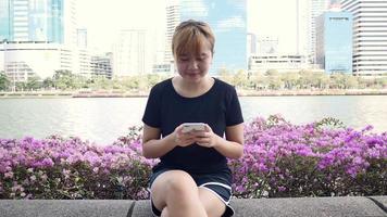 linda jovem asiática sentada no banco do parque usando o smartphone para conversar, ler e enviar mensagens de texto. video