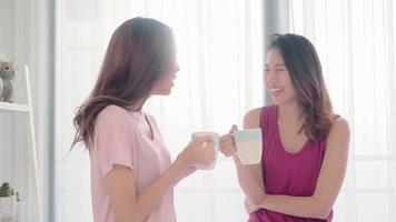 jóvenes amigos asiáticos tomando café en casa.