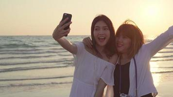 Young Asian friends taking a selfie on the beach.