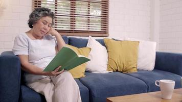 Asian elderly woman reading a book in the living room at home. video