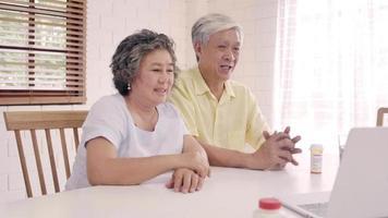 casal de idosos asiáticos usando um laptop
