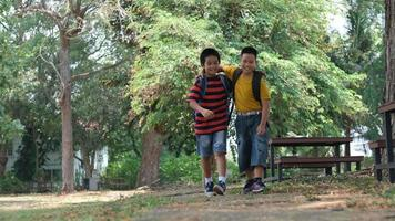 zwei Jungen von der Grundschule gehen mit ihren Rucksäcken spazieren video