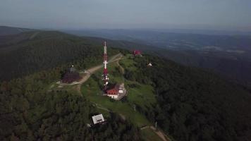 drone volando hacia una torre de radio e iglesia en 4k