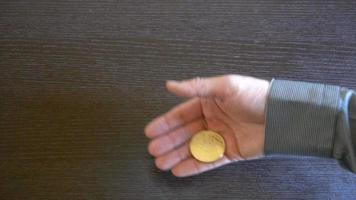 Golden Bitcoin in a man's hand. Symbol of a new virtual currency