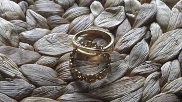 Accesorio de anillos de boda acostado sobre una mesa de paja