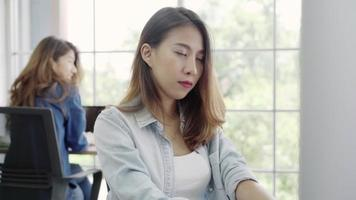 Joven mujer asiática trabajando en un portátil en una oficina.