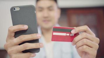 Hombre asiático usando un teléfono inteligente para compras en línea