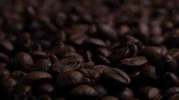 grãos de café torrados castanhos caindo em uma pilha