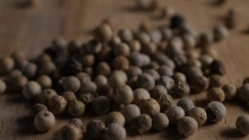 granos de pimienta sobre la mesa de madera video