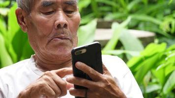 homem idoso deslizando em seu smartphone video