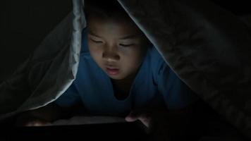 Niño usando tableta debajo de la manta por la noche en la cama video