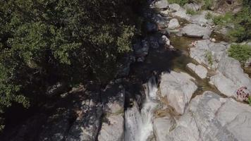 Drone descending to a waterfall on a sunny summer day in Corsica
