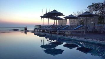 Outdoor swimming pool with sea view at sunset