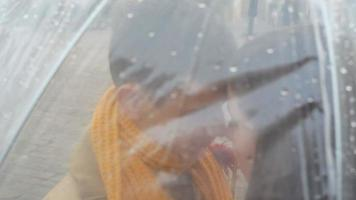 pareja joven de pie bajo un paraguas