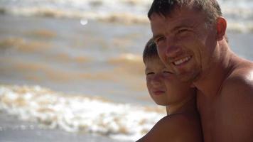 pai na praia com dois filhos