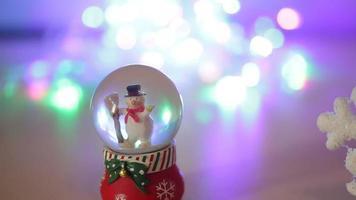 muñeco de nieve de juguete sobre un fondo plateado brillante