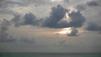 puesta de sol detrás de las nubes y sobre el mar