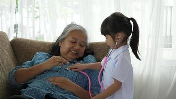 Little Girl Dressed As A Doctor Plays With Grandma