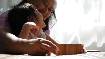 abuela y nieta juegan con bloques de jenga