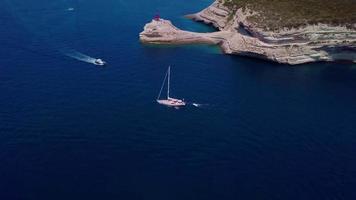 Drone follows a yacht in a bay in 4K
